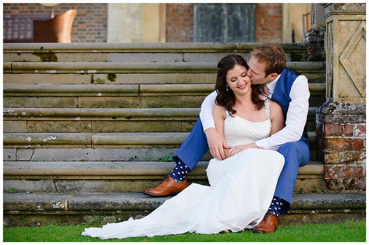 Madingley Hall Wedding groom kisses brides cheek whilst sitting on steps