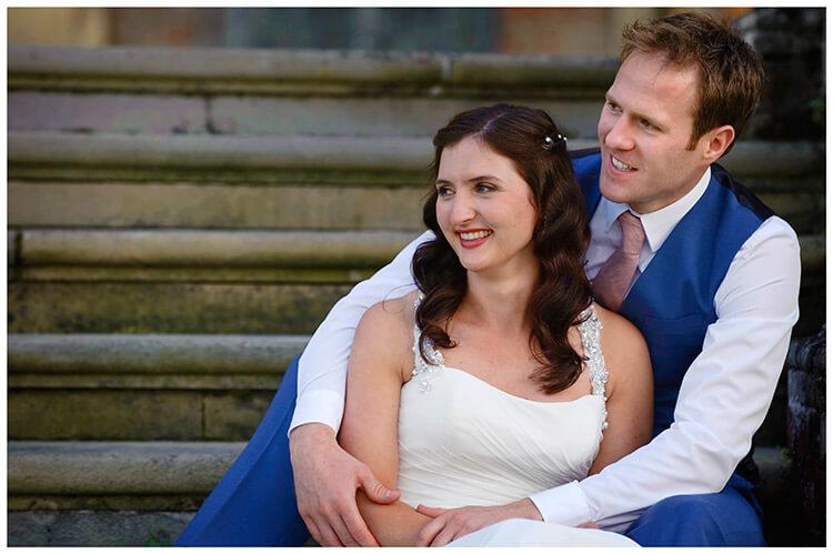 Madingley Hall Wedding bride groom embrace sitting on steps