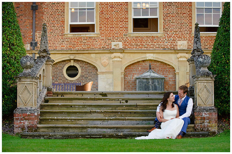 Madingley Hall Wedding bride groom sitting on steps smiling at each other