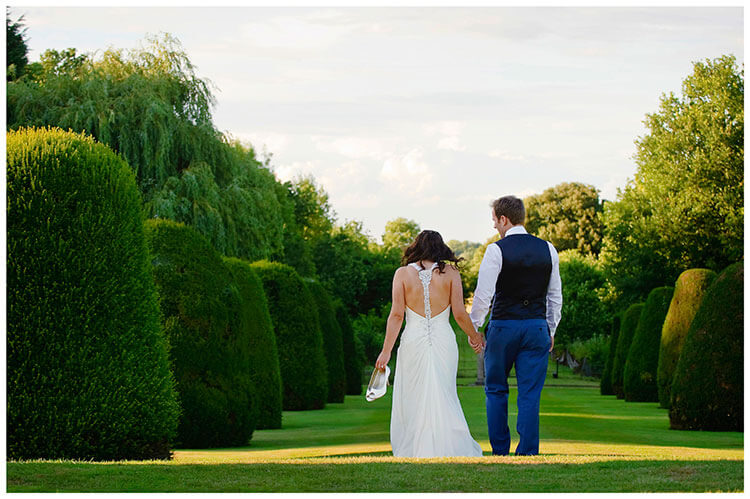 Madingley Hall Wedding bride holding shoes going for a walk with groom in gardens