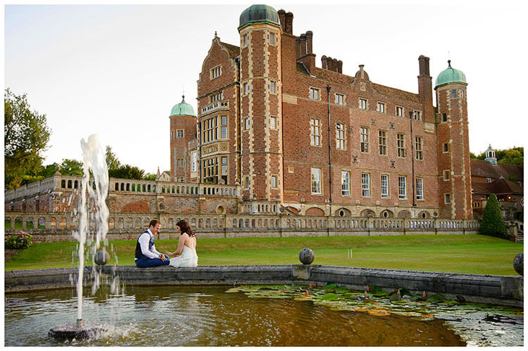 Madingley Hall Wedding bride groom sitting on fountains edge looking at wedding ring