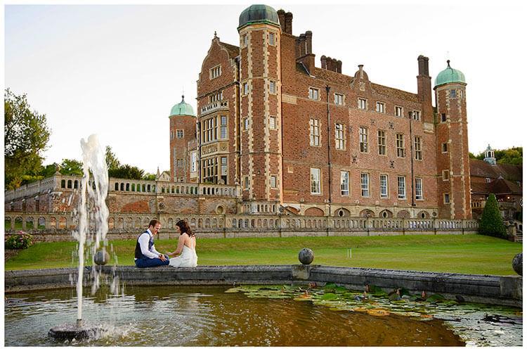 Madingley Hall Wedding bride groom sitting on fountains edge looking at wedding ring