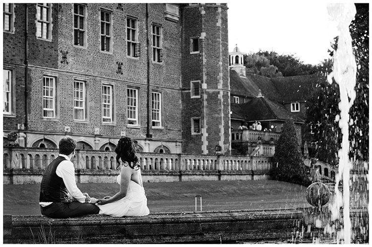 Madingley Hall Wedding bride groom sitting on fountain looking towards party guests