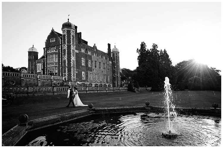 Madingley Hall Wedding bride groom late evening walk near fountain