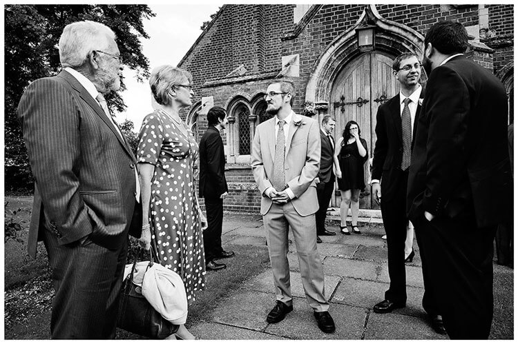 Groom talking to guests outside St John the Evangelist Church cambridge