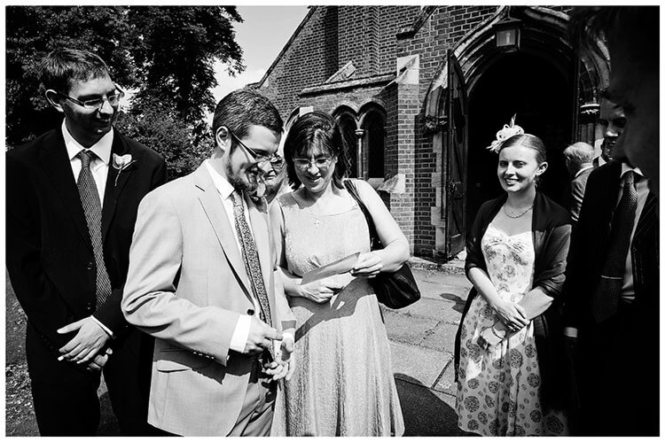 groom with guests out side St John the Evangelist Church cambridge