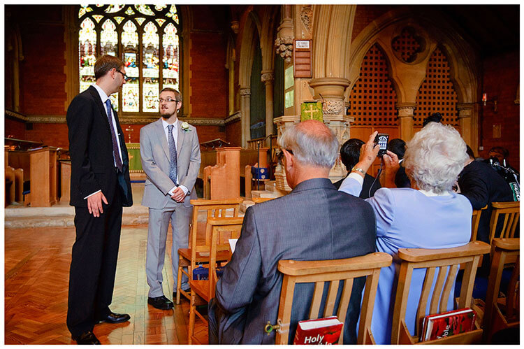 Groom bestman in church guest takes photo of church window