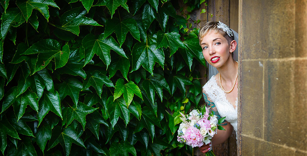 creative documentary wedding photographer cambridge trinity college uk europe bride peaking out of doorway green leaves