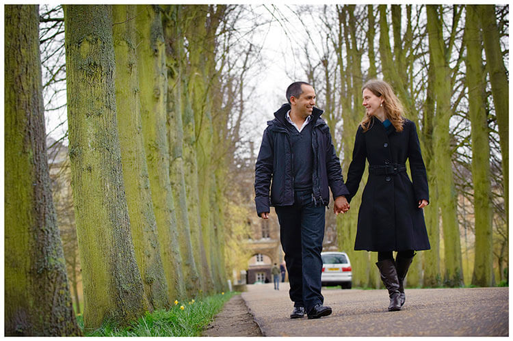 Cambridge Pre Wedding Photography couple walking along tree line avenue holding hands smiling