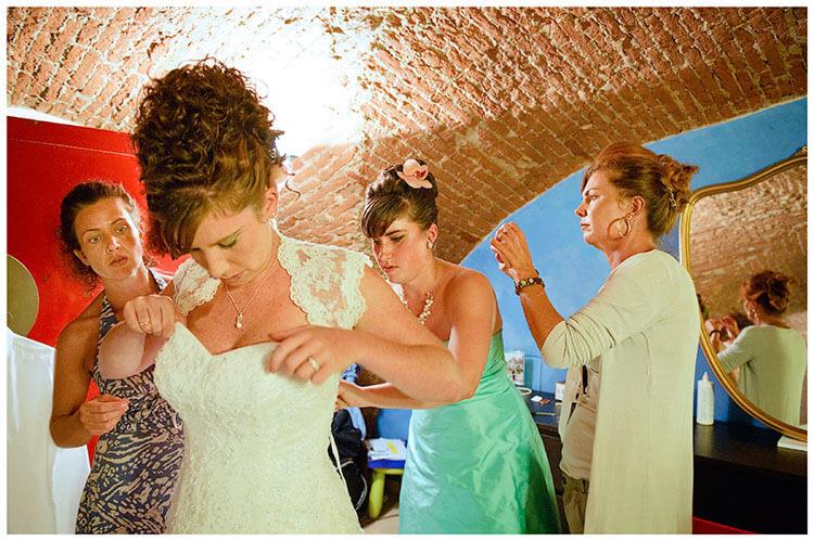 Castel di Poggio wedding bride getting into dress