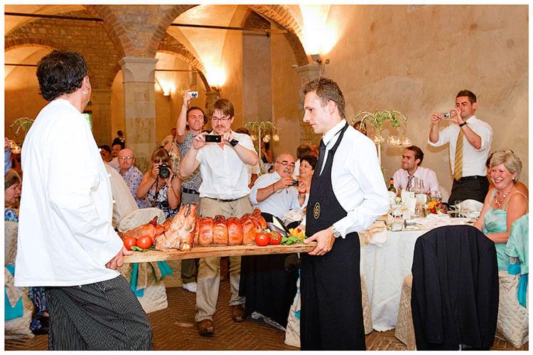 Castel di Poggio wedding taking photos of suckling pig for dinner
