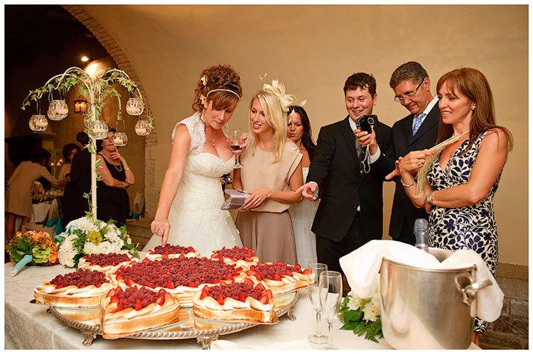Castel di Poggio wedding bride picks a fruit from the spectacular wedding cake