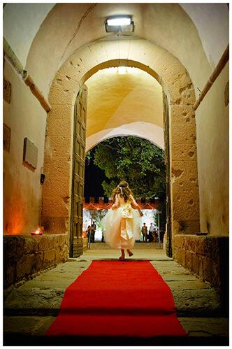 Castel di Poggio wedding flower girl running along red carpet