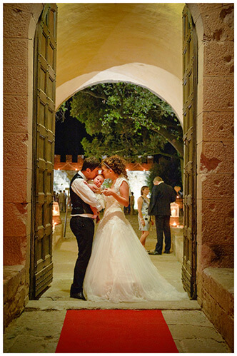 Castel di Poggio wedding bride groom in doorway kissing baby flower girl