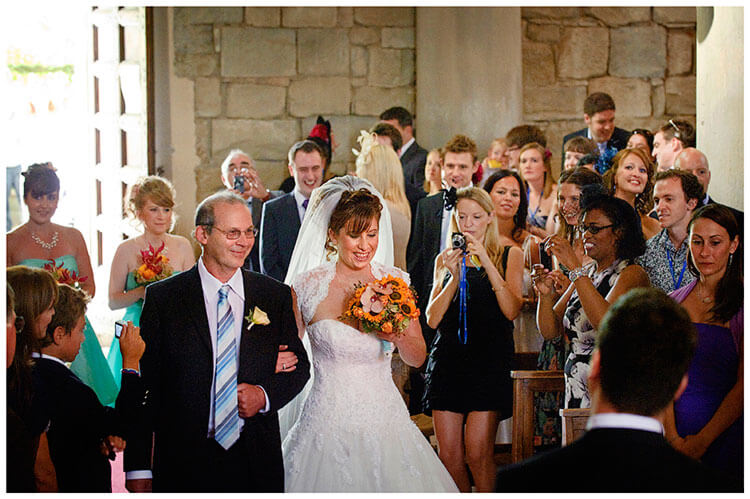 Fraternita di Romena wedding bride enters on fathers arm guests take photos