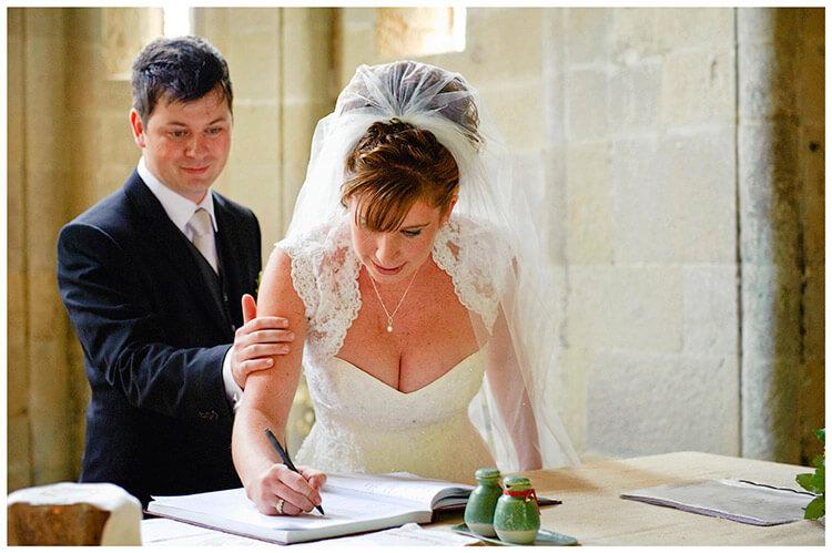 Fraternita di Romena wedding resuring hand from groom as bride signs register