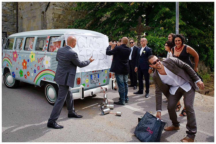 Fraternita di Romena wedding guests tying sign to back of blue VW Camper