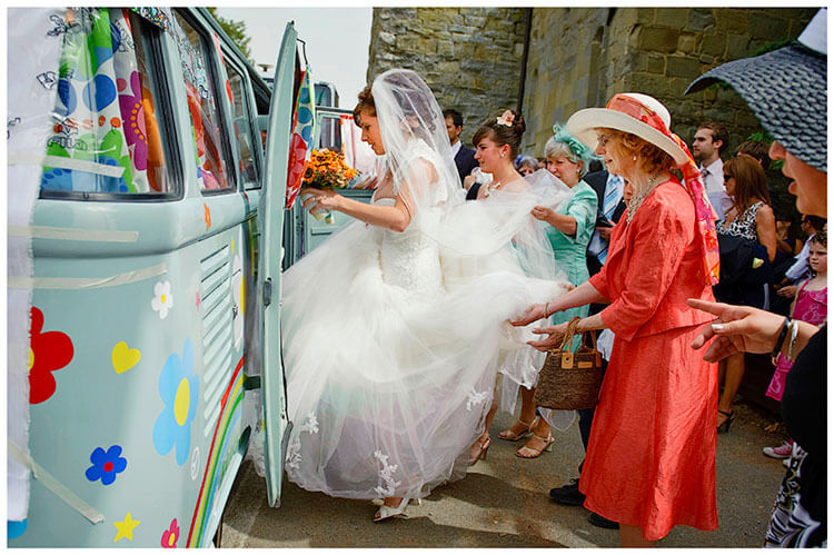 Fraternita di Romena wedding bride getting into VW camper assisted by female guests