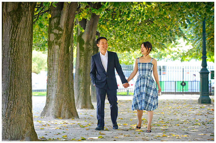 Paris pre-wedding photography laughing couple hold hands as they walk along tree lined arcade
