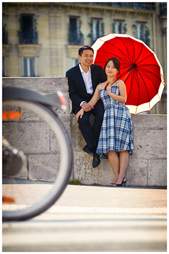 Paris pre-wedding photography couple under red umbrella as bicycle passes