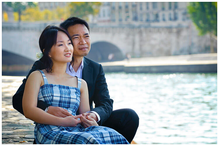 Paris pre-wedding photography couple sitting on banks of river seine