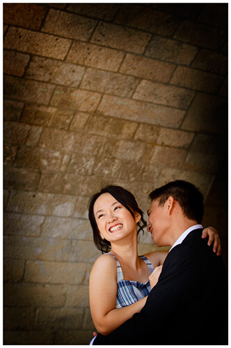 Paris pre-wedding photography smiling couple embrace under bridge