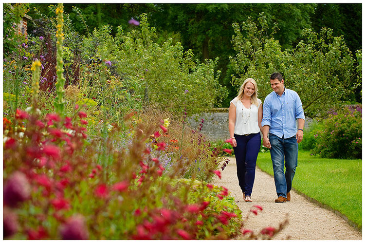 Pre Wedding Photography at Wimpole Hall Vicky and Dan walking hand in hand along garden path