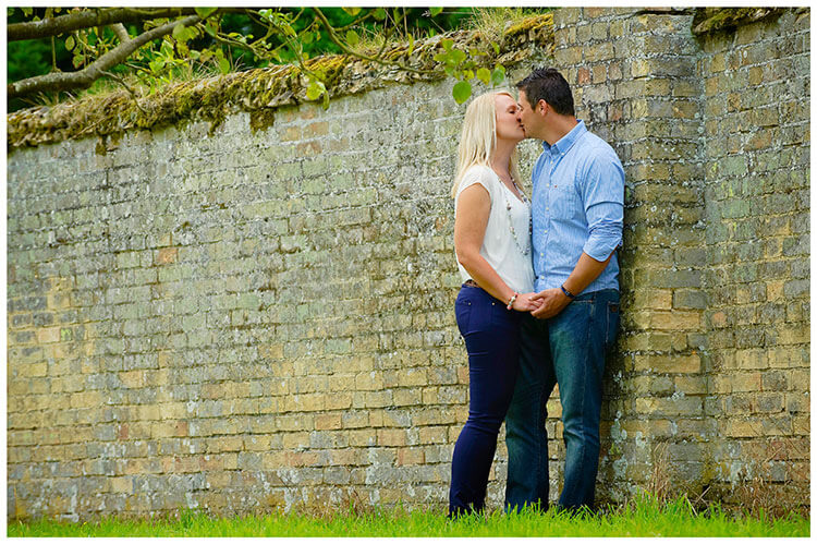 Pre-Wedding Photography at Wimpole Hall couple kiss standing next to wall