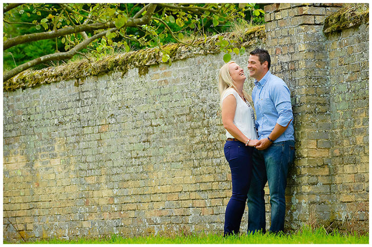 Pre-Wedding Photography at Wimpole Hall laughing couple standing next to wall