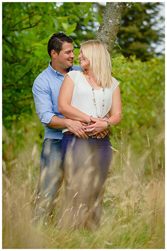 Pre-Wedding Photography at Wimpole Hall couple gaze at each other in long grass