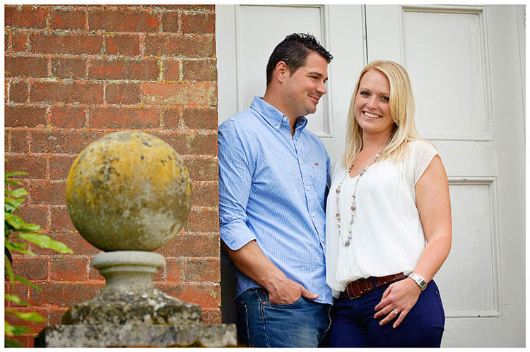 Pre-Wedding Photography at Wimpole Hall Dan looks at Vicky leaning against wall in doorway