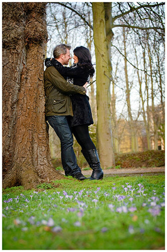 pre-wedding photography Cambridge couple embrace leaning against tree small purple flowers in foreground