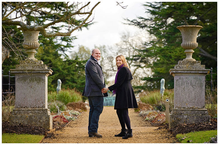 Sculpture Gallery Pre-Wedding photography kate andy walking on footpath looking backwards between two grand flower pots in gardens