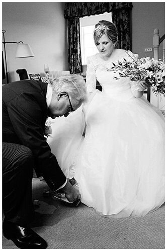 Woburn wedding brides father places shoe on her foot