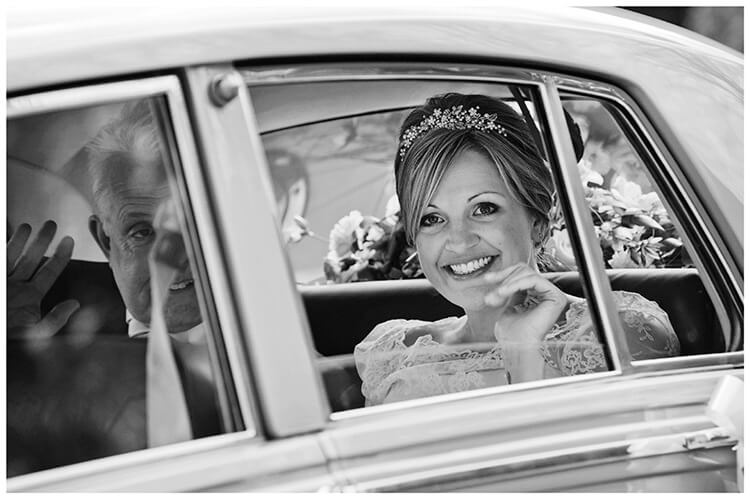 Woburn Church wedding smiling bride arrives in car waving