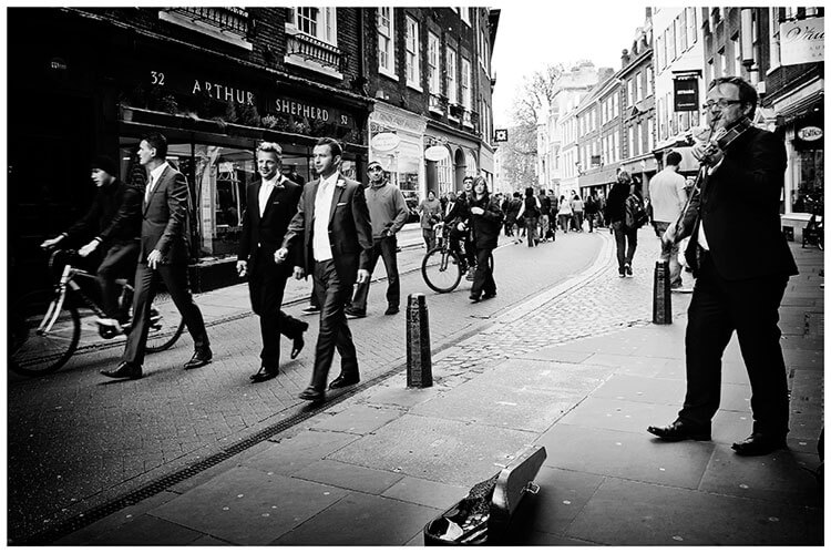 Christ's College wedding groom and groomsmen walking through streets of cambridge musician