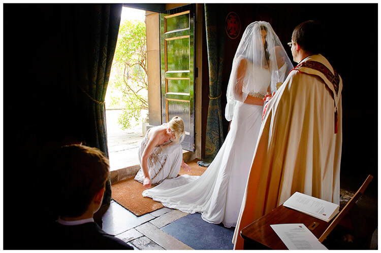 Christ's College wedding bride talks to vicar bridesmaid adjusts dress little boy watches