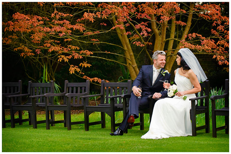 Christ's College wedding bride groom sitting on bench colorful foliage in background