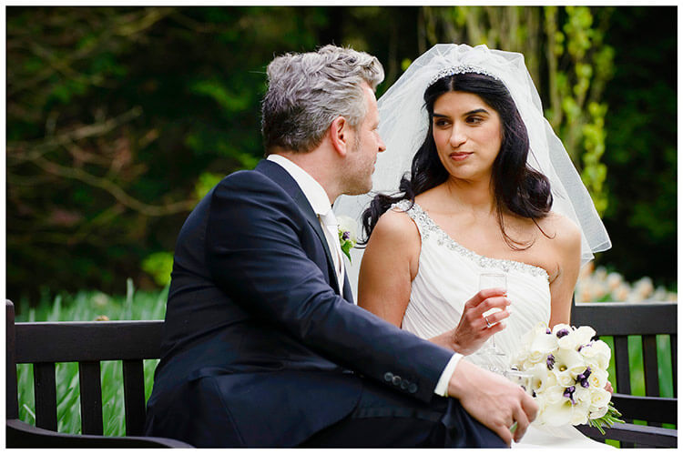 Christ's College wedding bride looking at her groom whilst they it on a bench