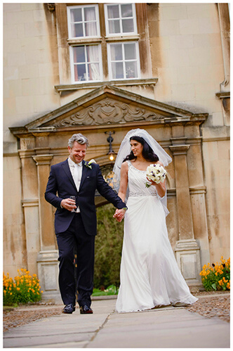 Christ's College wedding smiling bride groom hold hands as they walk along path