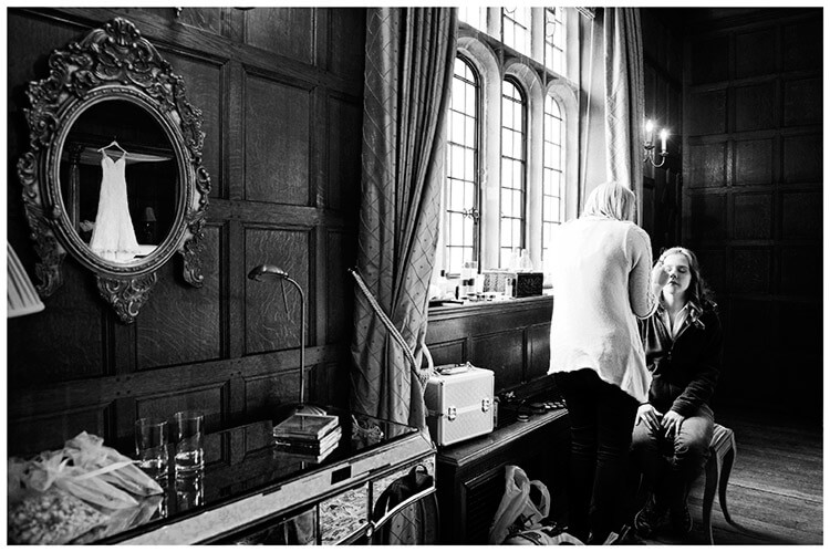 Wedding photography at Hengrave Hall bride having make up done dress reflected in mirror