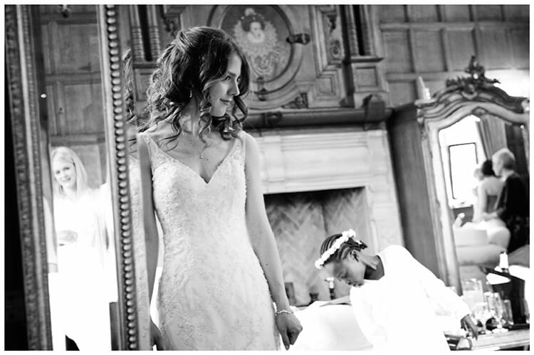 Wedding photography at Hengrave Hall bride flower girl reflected in mirror checking dresses