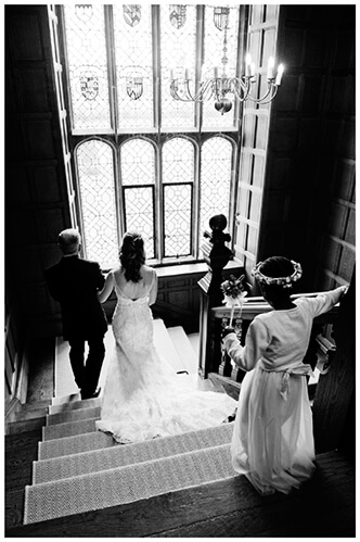 Wedding photography at Hengrave Hall bride and father walking down stairs followed by flower girl
