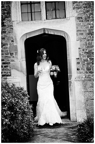 Wedding photography at Hengrave Hall bride champagne glass doorway