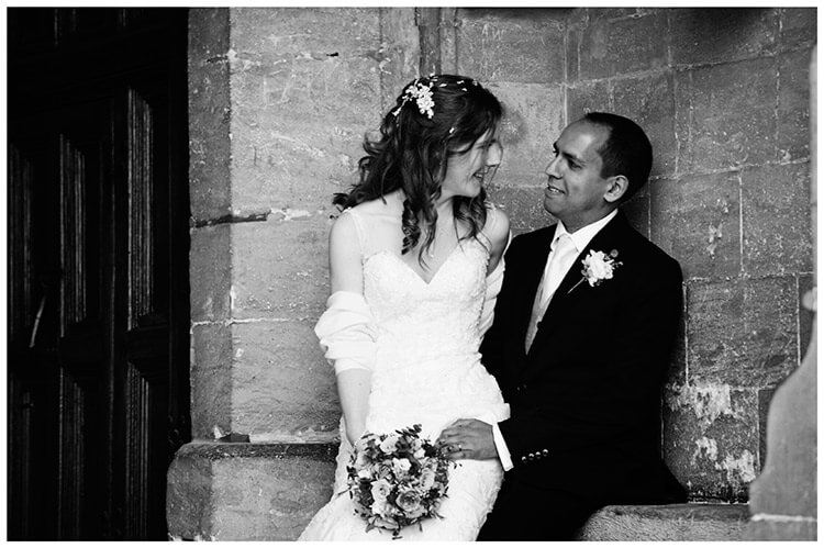 Wedding photography at Hengrave Hall bride sitting on grooms knee