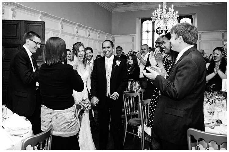 Wedding photography at Hengrave Hall bride groom enter to applause