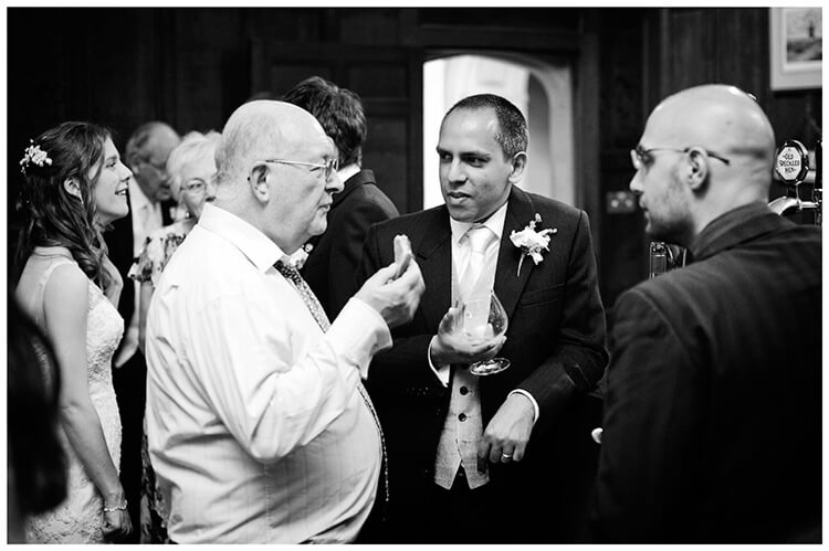 Wedding photography at Hengrave Hall enjoying drinks food and conversation