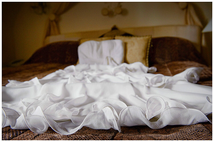 Sheene Mill wedding Bridal dress laid out on bed