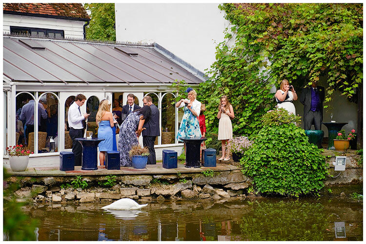 Sheene Mill wedding guests near waters edge swan swims by