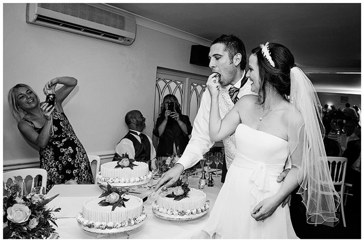 Sheene Mill wedding bride feeds a piece of cake guest takes photo